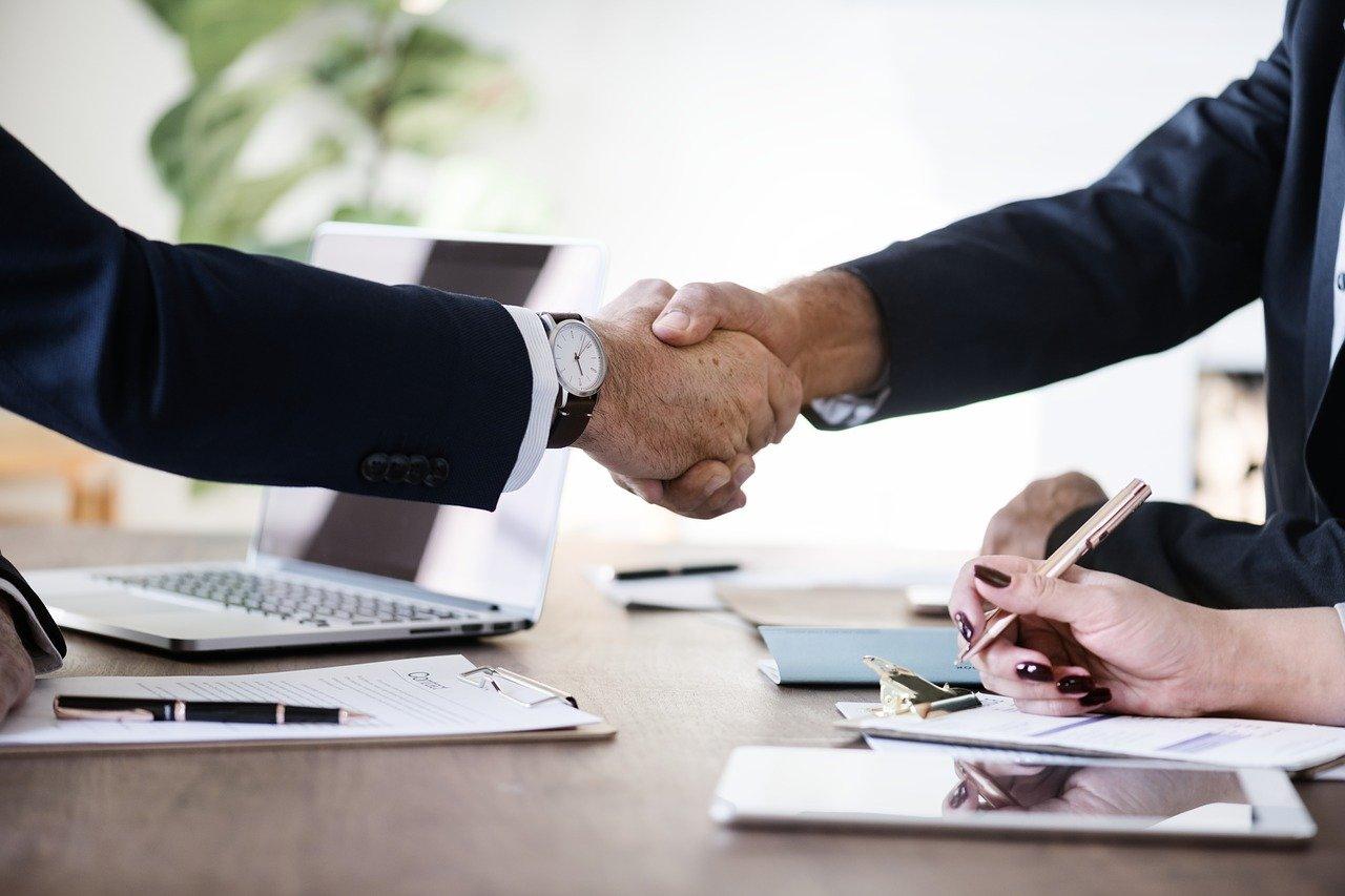"""Focus sur la poignée de main de deux business man conclouant un accord, au-dessus d'un bureau et d'un ordinateur. Illustre l'article """"16ème dialogue Etats-Unis – Union Européenne : échanges autour de grandes problématiques numériques"""""""